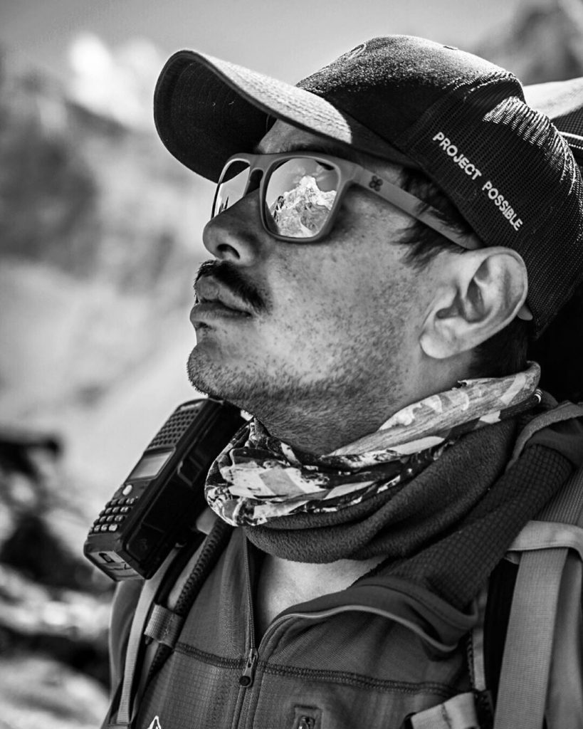 picture of Nirmal Purja in black and white with a reflection of the mountains over his sunglasses