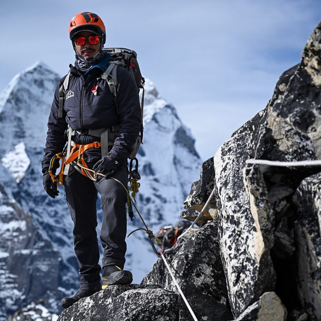 Black diamond helmet Vector used by Nirmal Purja while climbing the mountain with a snowy mountain in background