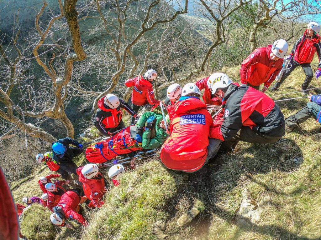 rescue team carry injured person in mountain